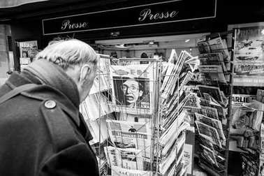 Senior man buying French newspaper Liberation at Parisian press