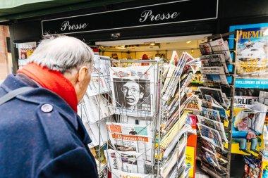 Senior man buying French newspaper Liberation at Parisian press