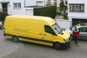 Paříž, Francie - 30 březen 2018: Mužské Courier zadá žlutá dodávka Dhl po doručení na čas doručení balíčku pozemek v typické Evropské sousedství - pohled