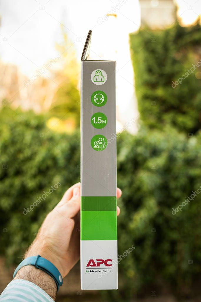 PARIS, FRANCE - MAR 31, 2018: Man holding against green background the side part of the box of an APC UPS power strip with four power outlets