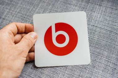PARIS, FRANCE - MAR 31, 2018: Man unboxing new Apple Beats By Dr Dre Beats Wireless headphones looking at the red iconic sticker