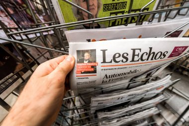 POV man holding Les Echos newspaper with Stephen Hawking portra