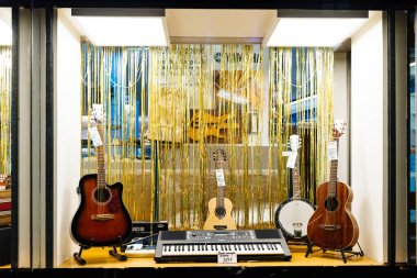 Musical store showcase selling four guitars and piano