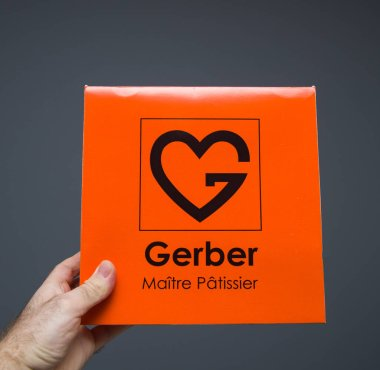 POV of man hand holding against gray background package of ca cake manufactured by Gerber Maitre patissier in Strasbourg France