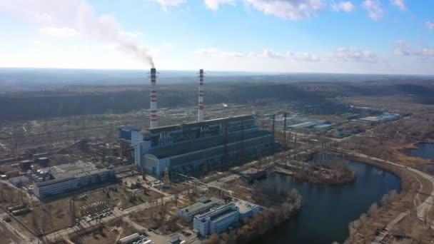 Letecký pohled na vysoké komínové trubky s šedým kouřem z uhelné elektrárny. Výroba elektřiny z fosilních paliv.