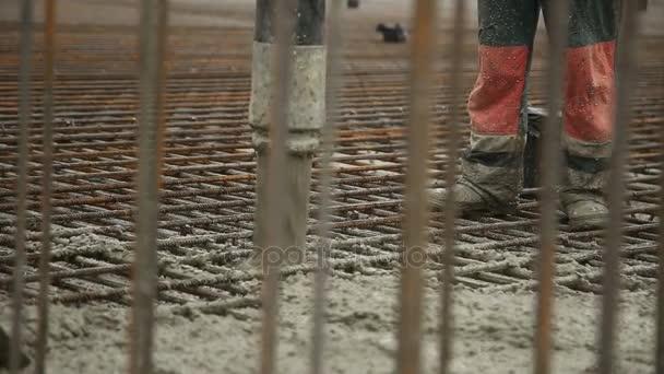 Lití betonové směsi z cement mixer na betonování bednění. Dokončení vyrovnání desky a lití betonu suterén