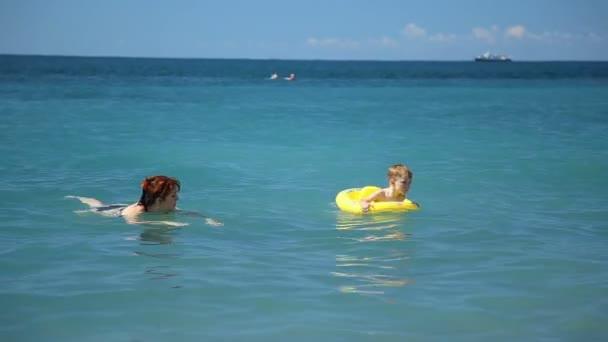 Matka a malý syn radost z hraní v moři. Žena točí vzrušený boy v gumovým kroužkem. Rodinná zábava během letních prázdnin