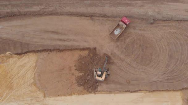 Baggerarbeiten im Industriebrachen. Eine Maschine mit Schaufel belädt einen LKW bei einer Karriere.