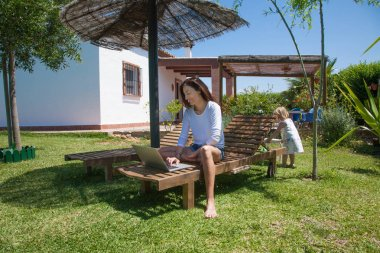 woman using laptop and little child at garden