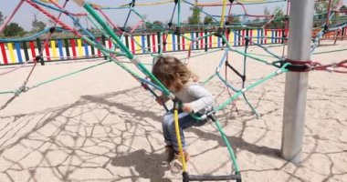 Child playing in ropes at playground with mother