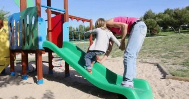 Mother teaching child to climb on slide
