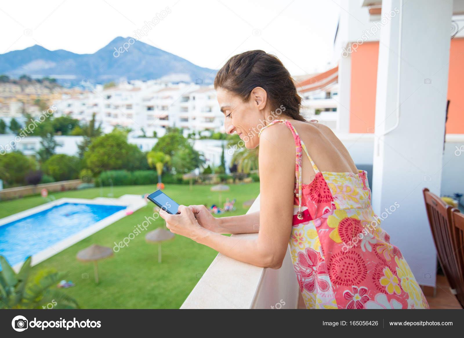 Frau Die Eingabe Auf Dem Handy Auf Der Terrasse Am Pool Stockfoto