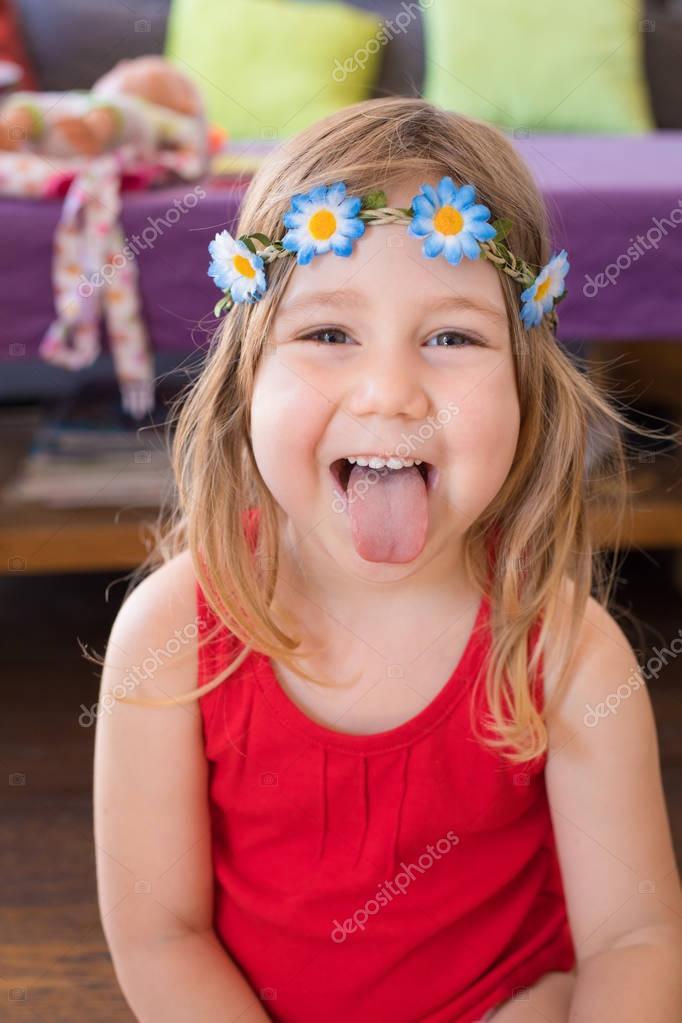 Portrait of hippie little girl sticking out tongue — Stock