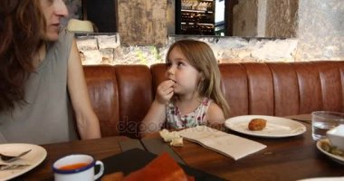 Little child eating olive talking to mother in restaurant