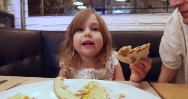 Little girl in restaurant speaking and eating pizza