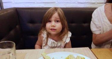 Little girl in restaurant speaking
