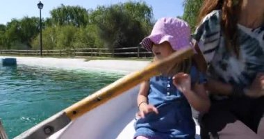Little girl playing with the oar in a boat