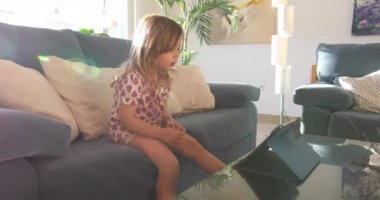 Little girl watching tablet with sunbeam