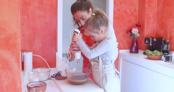four years old girl with pigtail and woman mother whipping with electric mixer a cocoa or chocolate cream into a crystal bowl
