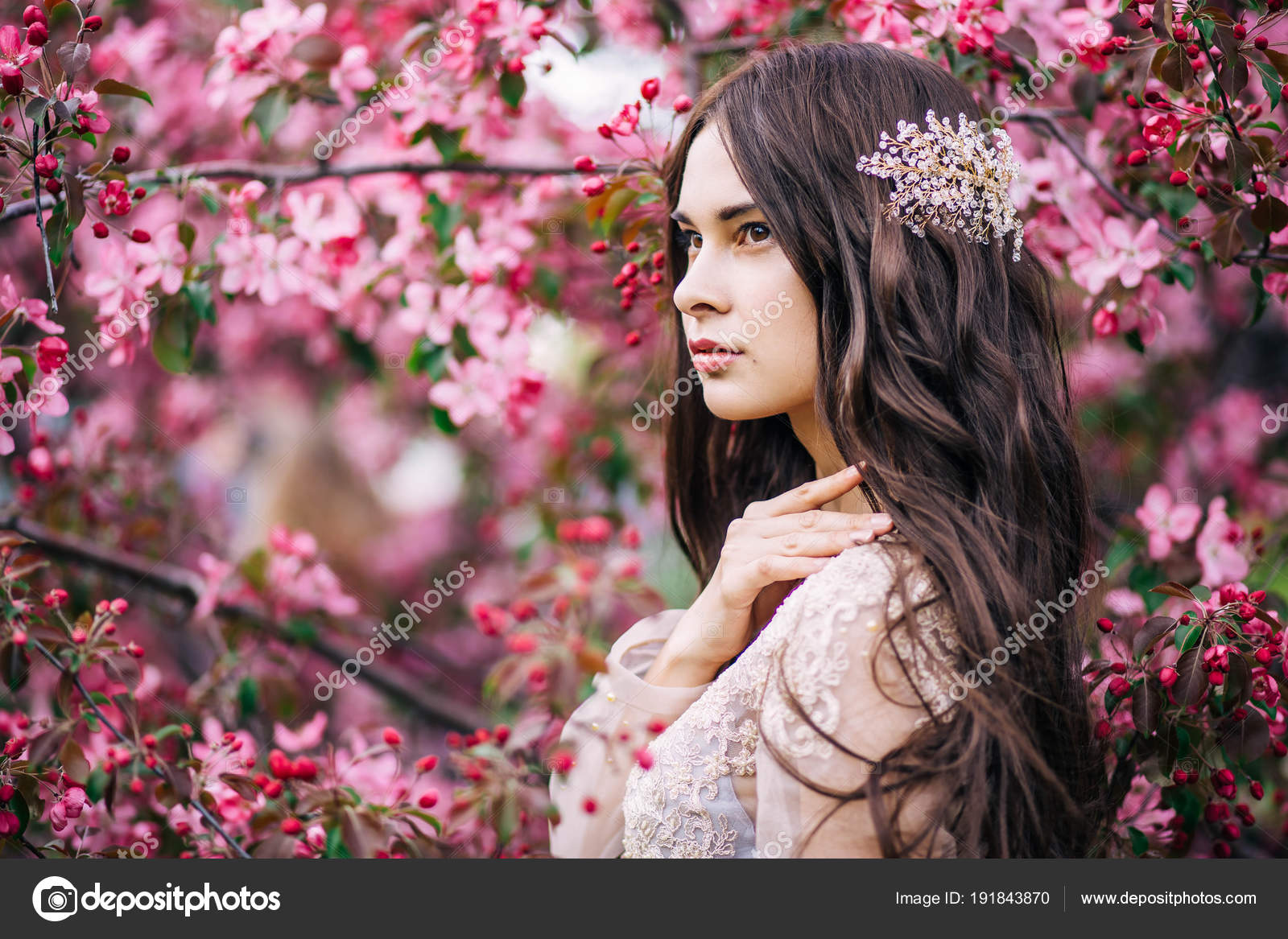 Beautiful cute brunette girl bride in boudoir lace transparent dress with decoration on the hair near the tree blossoms with pink flowers profile
