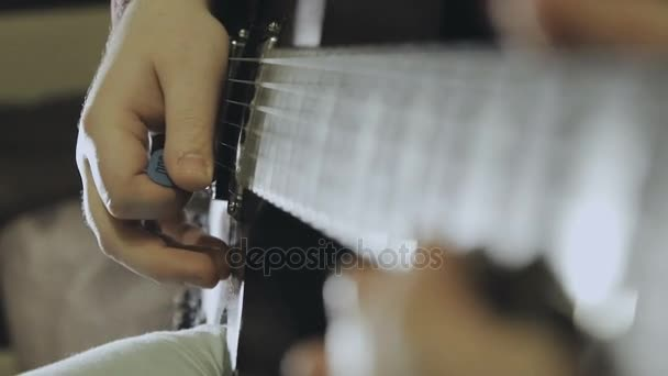 Člověk hraje na elektrickou kytaru, ruce detail