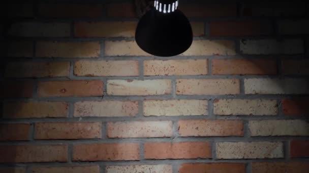 Žárovka svítí na cihlovou zeď, textury cihly.