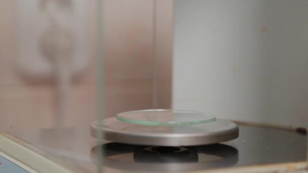 Lékárník váží lék na přesných vahách.
