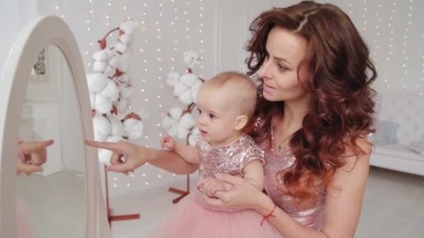 Krásná matka s jednoletou dcerou v krásných šatech a novoroční výzdobě. Nový rok 2020.