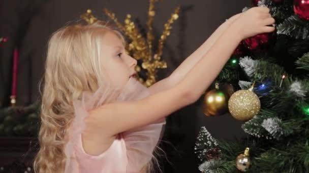 Desetiletá dívka poblíž novoroční stromku drží v rukou novoroční hračku. Nový rok 2020.