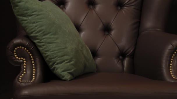 Elegantní syté lesklé zlaté kožené textury rozkládací židle, hnědá kůže pozadí.