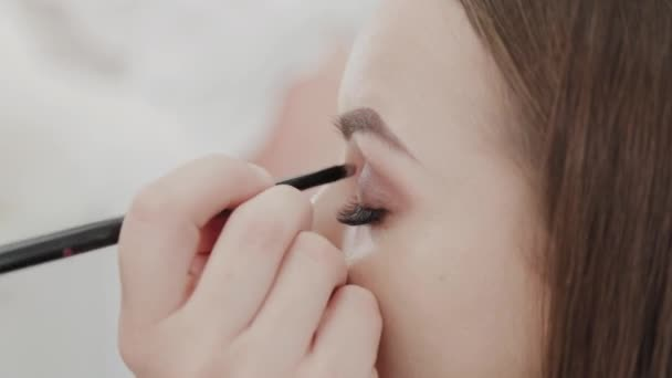 Professional makeup artist woman stirs makeup cream on a palette.