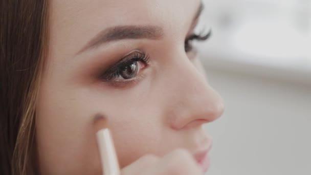 Szakmai sminkes nő keveri smink krém egy paletta.