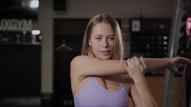 Atletická žena s krásnou postavu dělá protahování před tréninkem.