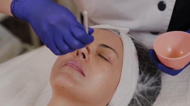 Professzionális kozmetikus alkalmazza arc szérum ecsettel.