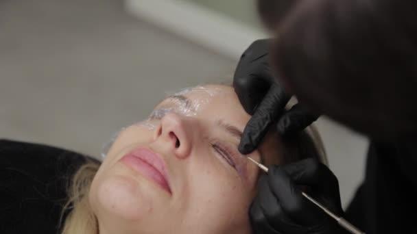 Profesionální kosmetička v salonu krásy maluje řasy na klienta.