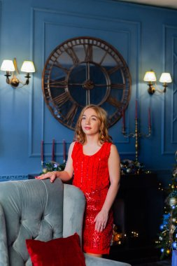 Beautiful happy young woman stands by the chair in the New Year decor.