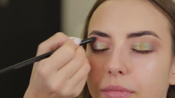Professional makeup artist puts eye shadow on a client of a beauty salon.