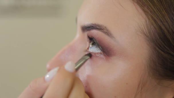 professioneller Maskenbildner legt Lidschatten auf Kundin eines Schönheitssalons.