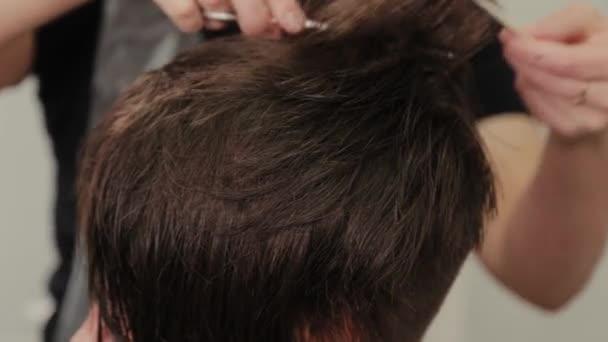 Profesionální kadeřnice dělá účes na mokré vlasy na klienta.