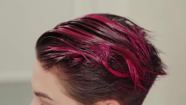 Profesionální kadeřnice dělá účes na klienta po barvení.