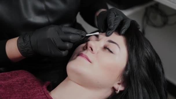 Profesionální permanentní vizážista nanáší anestetikum na obočí klienta.