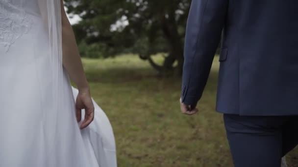 Šťastní novomanželé spojují ruce ve svatební den.
