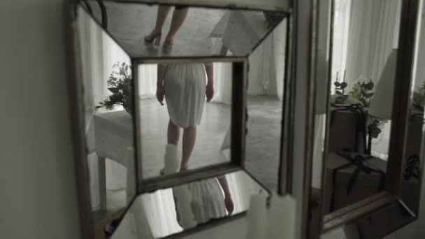 Krásná dívka se prochází po místnosti. Reflexe v zrcadle.