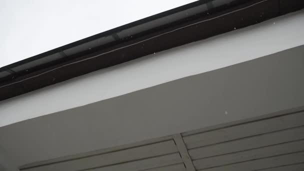 Dešťové kapky kapající ze střechy domu.