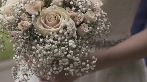 Nevěsta drží svatební kytici. Šťastný svatební den.