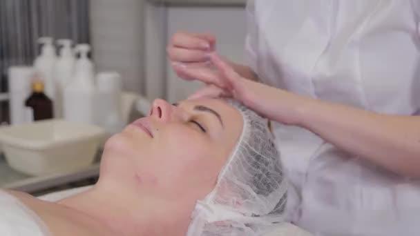 Professzionális kozmetológus nő, aki szérumot alkalmaz a betegek arcára.