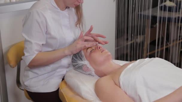 Profesionální kosmetička žena dělá masáž obličeje klientovi salonu krásy.