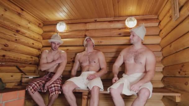 Pohlední fyzicky vyspělí muži vznášející se v sauně.
