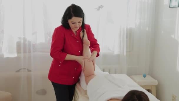 weibliche Massagetherapeutin massiert Klienten Beine.