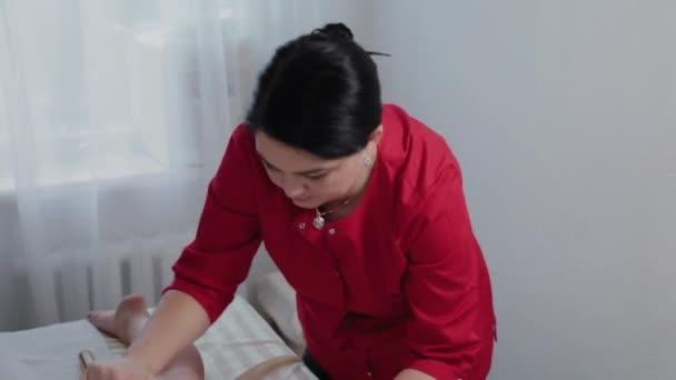 Női masszázs terapeuta csinál masszázs bambusz rúd ügyfél masszázs szalonban.